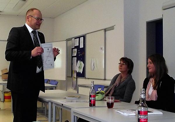 Ralf Kalb überreicht Anna Störmer eine Urkunde zu ihrem gelungenen Projekt...