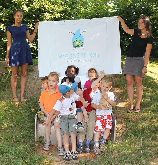 """Kindergartenleiterin Katja Tavman (rechts) und Renée Fofana (links) mit präsentieren mit den Kindern des Schulkindergartens das neue """"Wasserfloh""""-Logo."""