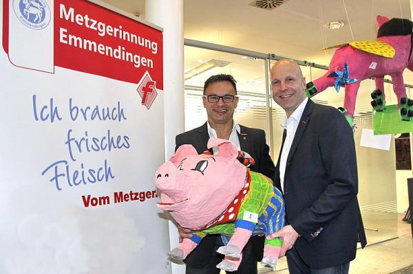 """Ausstellung """"Metzgerinnung sucht das Superschweinchen"""": Obermeister Gerhard Kaiser (links) und Stellvertreter Hans-Peter Rieger mit dem Sieger-Schweinchen  REGIOTRENDS-Foto: Reinhard Laniot"""
