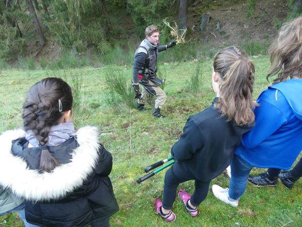 Landwirt Stefan Winterhalter erklärt Schülerinnen, wie man den Besenginster an der Wurzel entfernt. Foto: Biosphärengebiet Schwarzwald