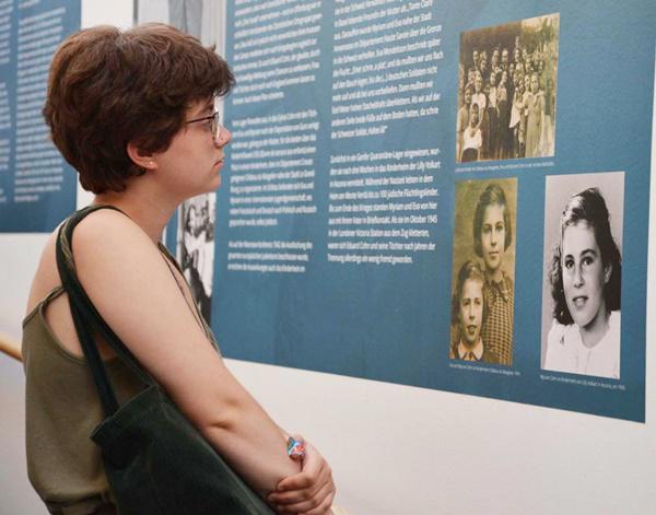 Myriam Burger im Salmen-Aufgang. Sie steht vor der Tafel, die die Geschichte ihrer Familie erzählt.  Foto: Klettner