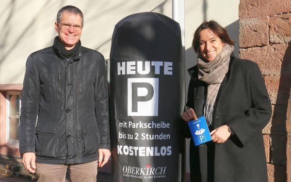 Oberkirch spendiert kostenloses Parken in der Vorweihnachtszeit. Bürgermeister Christoph Lipps und Iris Sehlinger stellten die neueste Aktion des Stadtmarketings vor. Immer wenn die Parkscheinautomaten mit den Hussen umhüllt sind, kann für zwei Stunden mit einer Parkscheibe kostenlos geparkt werden.  Foto: Stadt Oberkirch