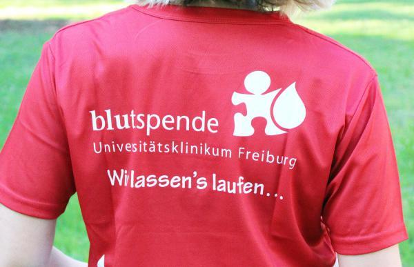 """Blut spenden und Laufshirt gewinnen. """"Wir lassen's laufen"""" steht auf den Laufshirts der Blutspendezentrale, die im Juli unter den Spender*innen verlost werden.  Foto: Universitätsklinikum Freiburg"""