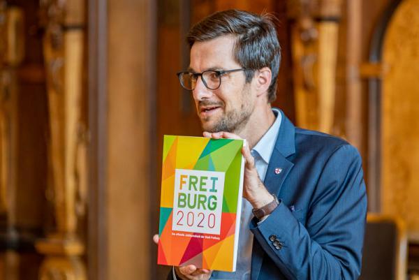 Stadt Freiburg stellte das Offizielle Jubiläumsbuch zur 900-Jahr-Feier vor. Oberbürgermeister Horn zeigt das neue Jubiläumsbuch.